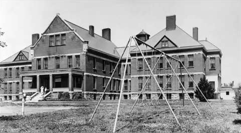 This black and white panoramic photograph shows the front of the Canton Asylum for Insane Indians (1899-1934). Narrow windows dot the four-story stone and brick building. A metal swing set stands in the front yard area; several people appear to be standing near the top steps of the front porch.