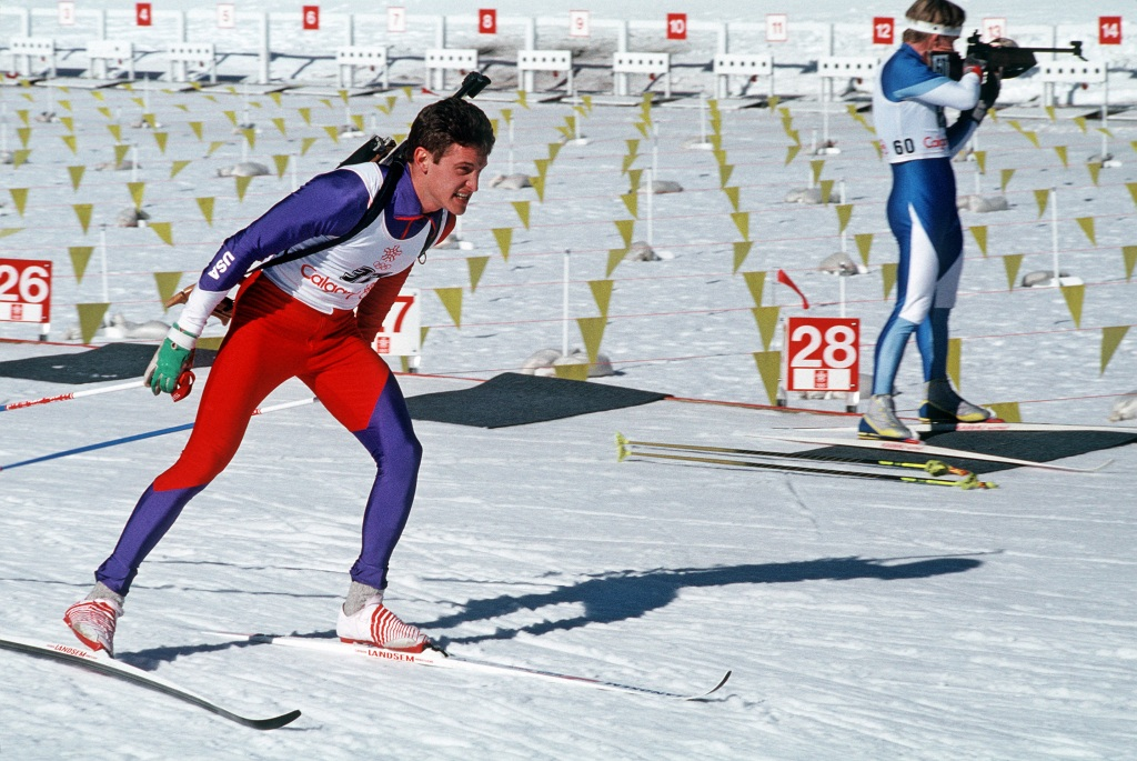 SPECIALIST Fourth Class (SPC) Curtis Schreiner, New York Army National Guard, skis toward the finish line as a competitior sights a target from standing position during the biathlon, part of the 1988 Winter Olympics, 02/13/1988. NARA ID: 6437944