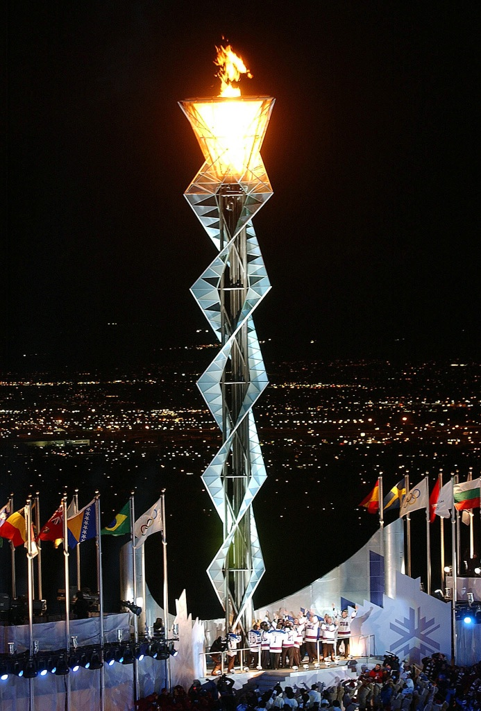 Members of the 1980 US Gold Medal Olympic hockey team stand below the Olympic flame after lighting it, at Rice-Eccles Olympic Stadium, during the opening ceremonies of the 2002 WINTER OLYMPICS in Salt Lake City, 02/08/2002. NARA ID: 6527810