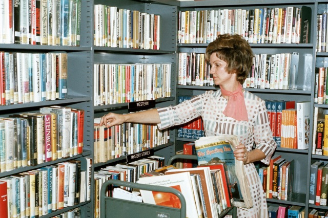 Mildred C. Crabtree, a civilian librarian, selects books in the library. 7/7/1976
